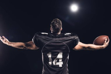 rear view of american football player with ball looking up with outstretched hands under spotlight on black