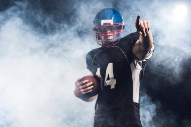 handsome american football player with ball pointing somewhere against white smoke
