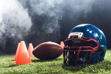 close-up shot of american football helmet with cones and ball on green grass with white smoke above