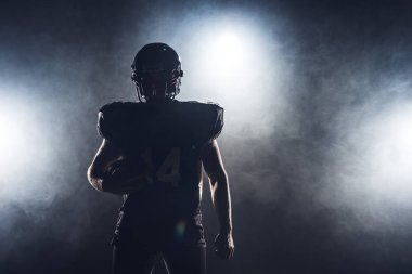 dark silhouette of equipped american football player with ball against white smoke