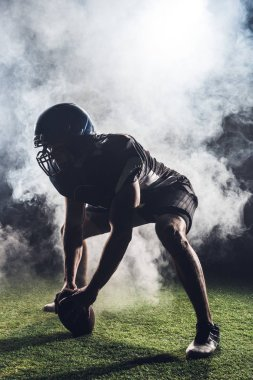silhouette of athletic american football player in star position against white smoke