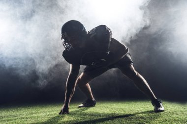 silhouette of american football player in star position against white smoke