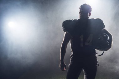 silhouette of american football player in uniform against white smoke
