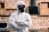 Fotografie pest control worker standing in uniform with crossed arms in kitchen