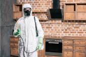 Fotografie pest control worker standing with sprayer in kitchen