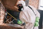 Photo pest control worker spraying pesticides on metal shelves in kitchen