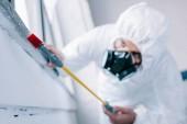 Fotografie pest control worker spraying pesticides under windowsill at home
