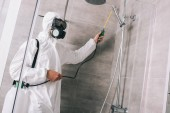 Fotografie pest control worker spraying pesticides with sprayer in bathroom