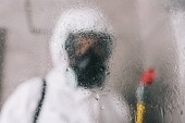 Fotografia pest control worker standing in respirator in bathroom