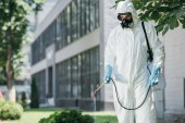 Fotografie pest control worker in uniform and respirator spraying pesticides on street with sprayer