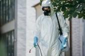 Photo pest control worker spraying pesticides on street with sprayer
