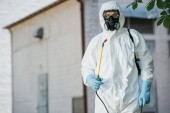 pest control worker in respirator holding sprayer