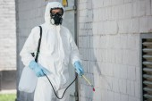 pest control worker in respirator spraying pesticides with sprayer on building wall