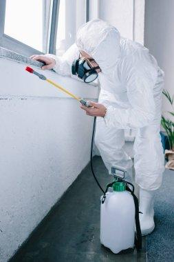 pest control worker in uniform spraying pesticides under windowsill at home