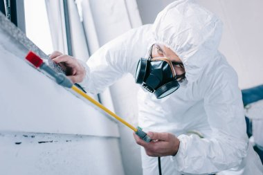 pest control worker in respirator spraying pesticides under windowsill at home