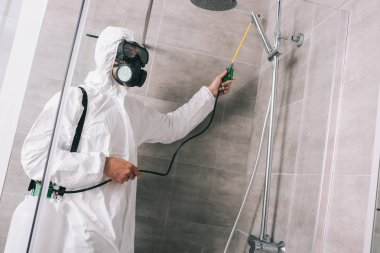 pest control worker spraying pesticides with sprayer in bathroom