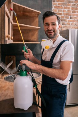 smiling pest control worker holding sprayer in kitchen