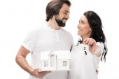 Fotografie selective focus of smiling couple with house model and keys isolated on white