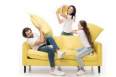 Fotografie happy family in white shirts on yellow sofa having pillow fight isolated on white