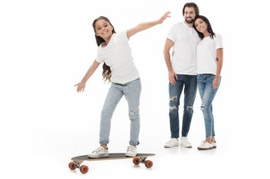 smiling parents looking at daughter skating on skateboard isolated on white