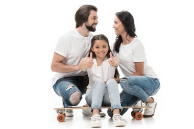 smiling kid sitting on skateboard and showing thumbs up with parents behind isolated on white