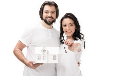 Portrait of smiling couple with house model and keys isolated on white stock vector