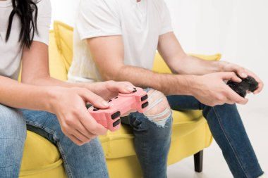 Partial view of couple with gamepads sitting on sofa isolated on white stock vector