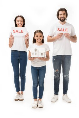 smiling family with sale cards and house model isolated on white