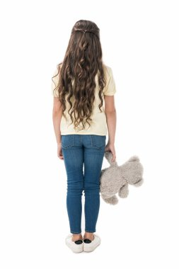 back view of little kid with teddy bear in hand standing isolated on white