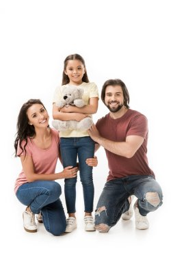 smiling parents and daughter with teddy bear isolated on white