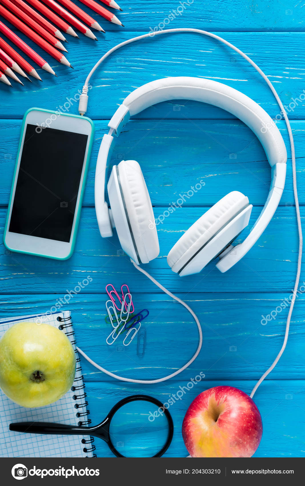 top view headphones smartphone blank screen apples stationery blue