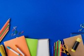 top view of empty textbook and variety stationery on blue background