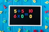 Photo top view of blackboard with math sums, colorful numbers and paper clips on blue wooden background