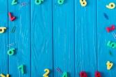 pohled shora na barevné různé čísla a sponky na modré dřevěné pozadí