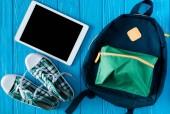 Fotografie pohled shora digitální tabletu s prázdnou obrazovkou, tenisky a batoh na modré dřevěné pozadí
