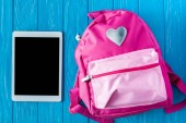 Fotografie top view of digital tablet with blank screen and pink backpack on blue wooden background