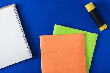 top view of blank notebook, glue stick and textbooks on blue background