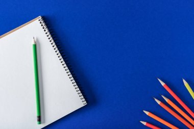 top view of arranged variety pencils and blank textbook on blue background