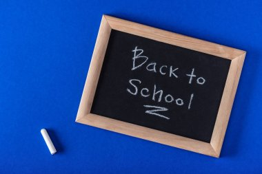 Top view of chalk and blackboard with lettering back to school on blue background stock vector