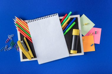 top view of blank notebook and empty blackboard with variety stationery on blue background