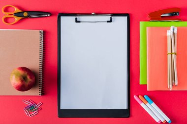 top view of empty clipboard, apple and arranged variety stationery on red background