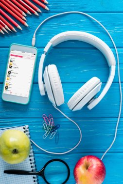 top view of smartphone with apple music application on screen, headphones, apples and stationery on blue wooden background