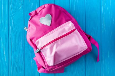top view of pink backpack on blue wooden background