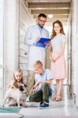 Fotografie children and mother choosing pug dog for adoption at animals shelter