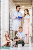 Photo veterinarian showing something in clipboard to woman, kids playing with pug dog at veterinary clinic