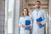 Photo two veterinarians in white coats walking with clipboards in veterinary clinic