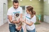Fotografie happy volunteers of animals shelter holding pug dog
