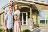 usmívající se rodiče a děti stojící před domem