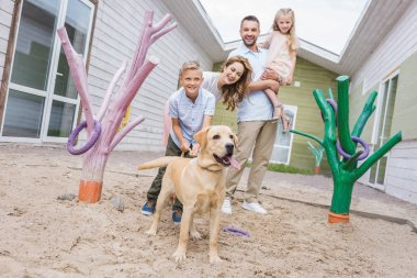 smiling parents and children standing with adopted labrador at animals shelter
