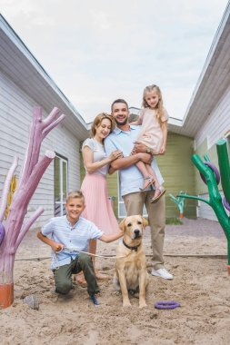 happy parents and children standing with adopted labrador dog at animals shelter